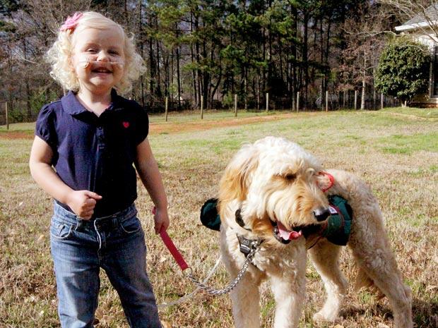 Alida Knobloch com Mr. Gibbs, o cão que carrega seu tubo de oxigênio (Foto: Caters News)