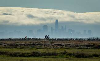 Bicyclists are in the foreground riding along the Hayward Regional Shoreline. In the background the San Francisco skyline is visible amid fog and clouds.