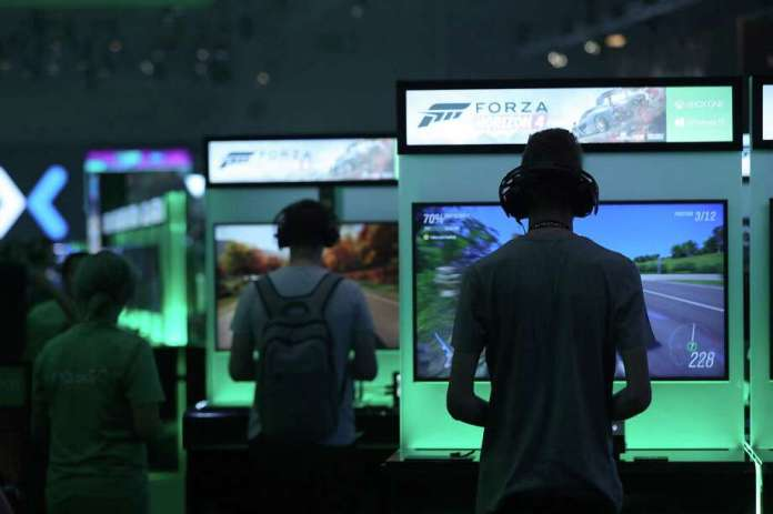"Gamers play ""Forza Horizon 4"" computer games using XBox consoles at the Microsoft stand at the Gamescom gaming industry event in Cologne, Germany, in August. Photo: Bloomberg Photo By Krisztian Bocsi / Bloomberg"