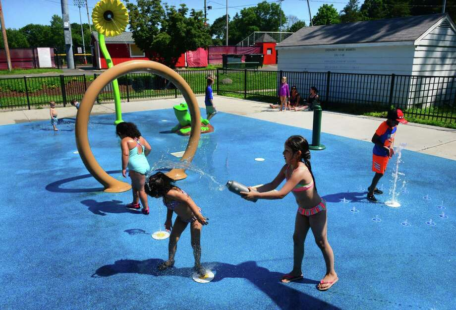 Jasmine Cabello, 8, of Stratford, throws water onto her little sister Nicole, 4, as they play at the spash pad at Longbrook Park in Stratford, Conn., on Tuesday July 10, 2018. The town is moving forward on putting another splash pad at Juliette Low Park. Photo: Christian Abraham / Hearst Connecticut Media / Connecticut Post