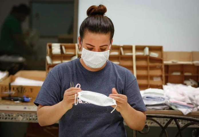 Maria Gonzalez inspects a facial mask at Paty, Inc. Thursday, March 26, 2020, in Houston. Paty, Inc. has been manufacturing clothing for 65 years, but since the new coronavirus has spurred demand for medical supplies, it has reorganized operations to produce face masks and surgical gowns. Photo: Steve Gonzales, Houston Chronicle / staff photographer / © 2020 Houston Chronicle