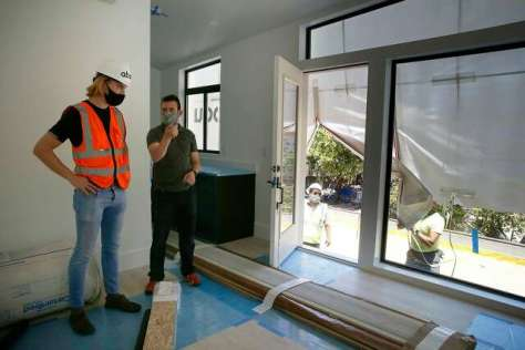 Eric McInerney (left), Abodu co-founder, talks with Omar Abi-Chachine, the son of the homeowner, inside the accessory dwelling unit after it was installed in Millbrae.