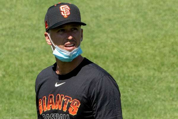 San Francisco Giants catcher Buster Posey (#28) wears a mask around his chin while participating in the San Francisco Giants' summer training camp session at Oracle Park in San Francisco, Calif. Saturday, July 4, 2020. Due to COVID-19, the 2020 MLB season has been postponed with players just beginning to return for warmups and practices while wearing masks and keeping social distance.