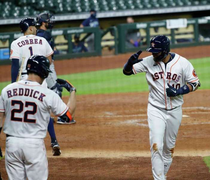 Houston Astros first baseman Yuli Gurriel salutes to Josh Reddick after his home run during the fourth inning of an MLB baseball game at Minute Maid Park, Saturday, July 25, 2020, in Houston.