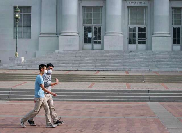 Two UC Berkeley students walk through Sproul Plaza wearing protective breathing masks on Nov. 16, 2018. The plaza was largely deserted after university officials canceled classes because of unhealthy air conditions caused by heavy smoke from the Camp Fire in Butte County.