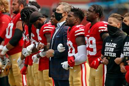 """49ers general manager John Lynch (center) stands among players on the goal line as """"Lift Every Voice and Sing"""" plays before the game."""