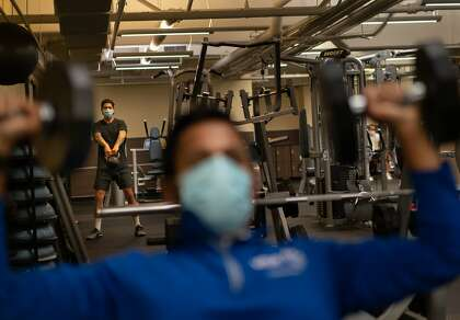 Frank Lavin (background) and Anush Vinod work on the new 24-hour fitness at 100 California St.