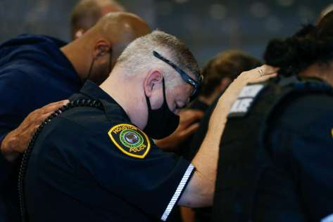 Houston Police officers embrace for a moment of prayer after learning Sgt. Harold Preston died at Memorial Hermann Hospital on Tuesday, Oct. 20, 2020, in Houston. Two officers were shot by a suspect during a domestic violence call at an apartment complex near El Rio and Holly Hall streets.