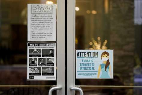 Signs posted on the door of the Luscious Salon in Lodi (San Joaquin County) advise customers about the pandemic guidelines. ICU capacity has dropped to zero in the greater San Joaquin Valley region.