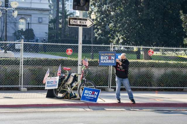 A supporter holding sign in support of president elect Joe Biden and Vice President Kamala Harris in front of the California Capitol in Sacramento, Calif. on Sunday, Jan. 17, 2021
