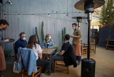 Sam Benson (left) serves water as co-partner Tanner Walle greets guests March 12 at Valley Bar & Bottle, a new wine shop, bar and restaurant in Sonoma.