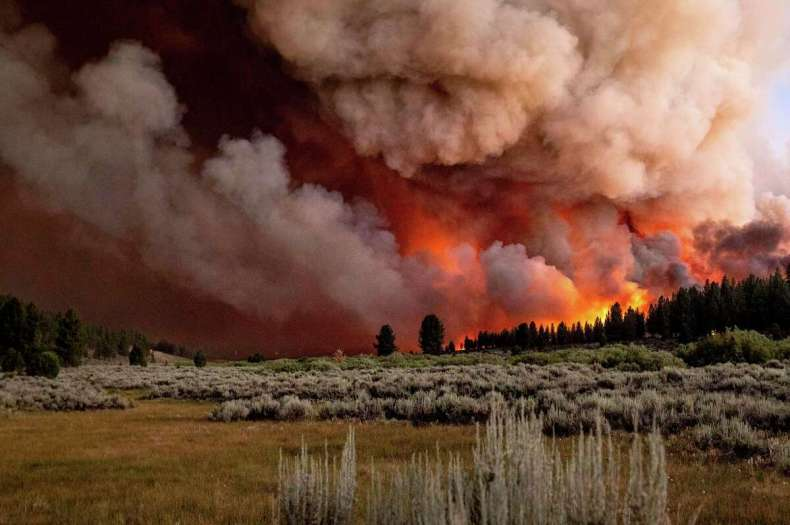 Plumes of smoke and fire rise above Frenchman Lake as the Sugar Fire, part of the Beckwourth Complex Fire, burns in Plumas National Forest.