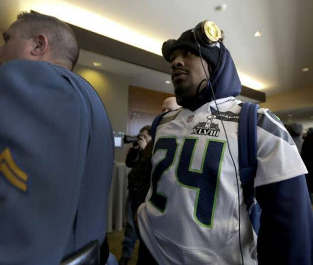 A Member Of The New Jersey State Police Escorts Seattle Seahawks Running Back Marshawn Lynch