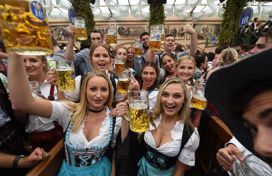 Oktoberfest 2016 kicks off in Munich   Houston Chronicle Visitors salute with beer mugs during the opening of the Oktoberfest beer  festival in a festival