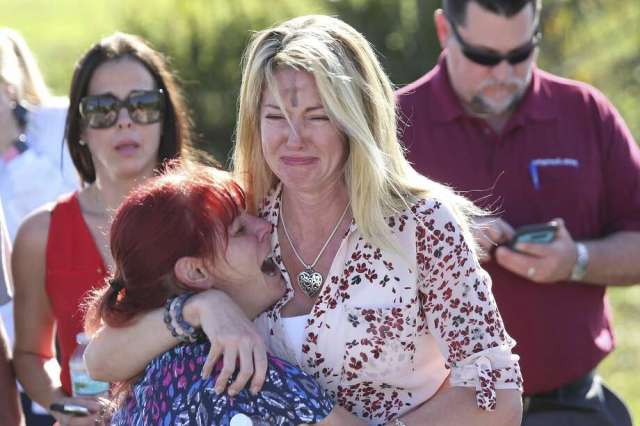 Parents wait for news after a reports of a shooting at Marjory Stoneman Douglas High School in Parkland, Fla., on Wednesday, Feb. 14, 2018. (AP Photo/Joel Auerbach) Photo: Joel Auerbach/AP