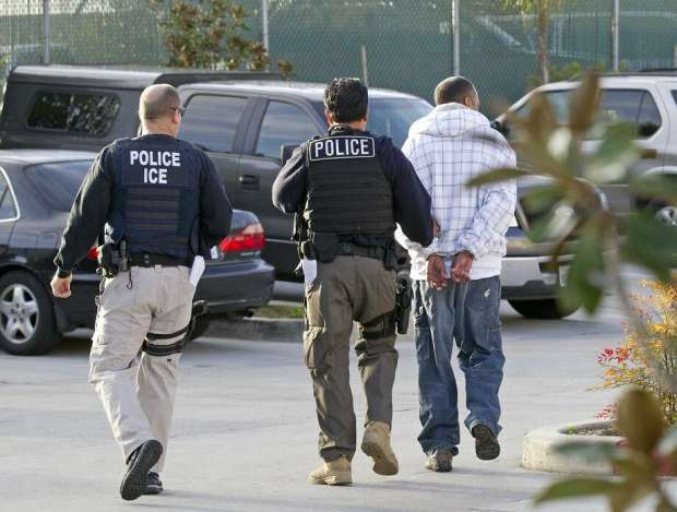 In this March 30, 2012 file photo, Immigration and Customs Enforcement (ICE) agents take a suspect into custody as part of a nationwide immigration sweep in Chula Vista, Calif. Photo: Gregory Bull, Associated Press