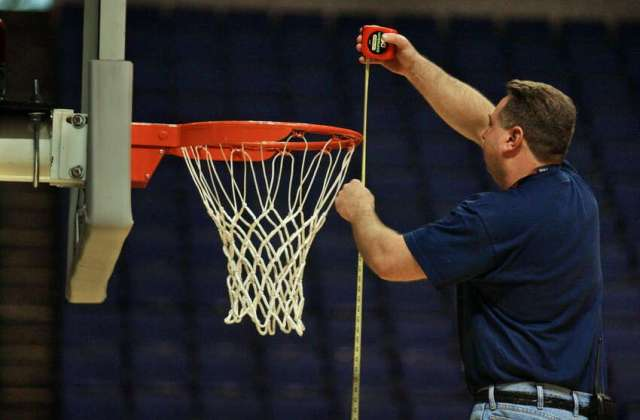 Pepsi Arena employee Gordon Derrick measures the height of one of the baskets (to make sure it is 10 feet high) at the Pepsi Arena in Albany pm March 26, 2003.