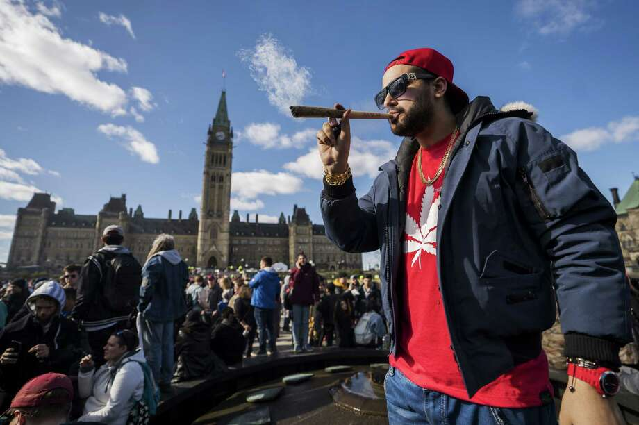 A resident smokes a large marijuana joint during the 420 Day festival on the lawns of Parliament Hill in Ottawa, Ontario, Canada, on April 20, 2018. Photo: Bloomberg Photo By Chris Roussakis / © 2018 Bloomberg Finance LP
