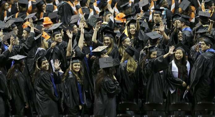 "University of Texas at San Antonio graduates wave to family and friends during the commencement ceremonies in December 2013 at the Alamodome. The Bureau of Labor Statistics says the value of a university degree is ""softening."" Photo: Edward A. Ornelas /San Antonio Express-News / © 2013 San Antonio Express-News"