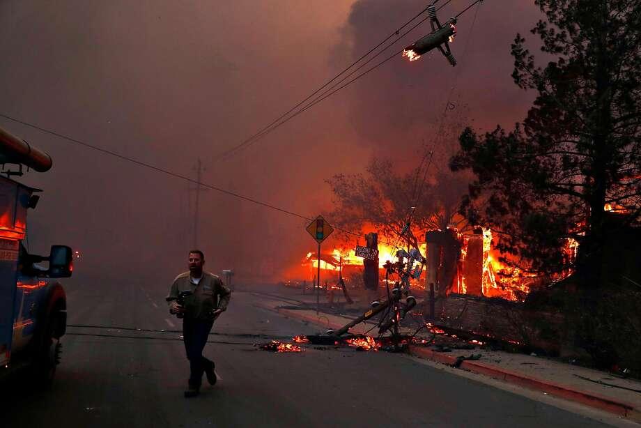 Un employé de PG & E travaille alors qu'il s'occupe de lignes électriques tombées en panne pendant un feu de camp à Paradise, en Californie, le jeudi 8 novembre 2018. Photo: Scott Strazzante / The Chronicle