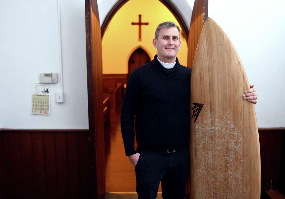 Rev. Matt Lindeman with one of his surfboards at St. Peter's Episcopal Church in Milford last week. Photo: Arnold Gold / Hearst Connecticut Media / New Haven Register