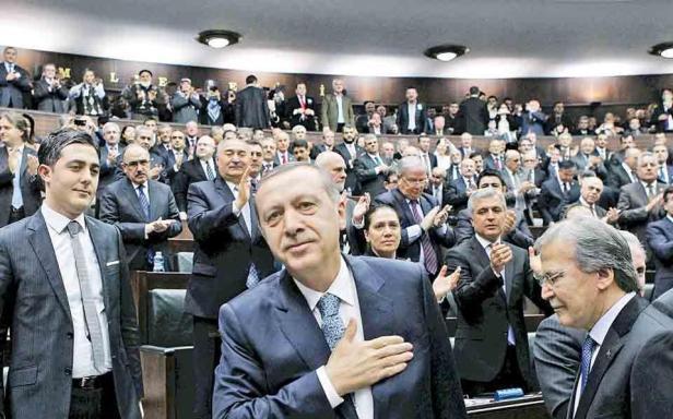 Πολιτικό σεισμό προκαλούν στην Τουρκία οι ηχογραφημένες συνομιλίες του πρωθυπουργού Ερντογάν με τον γιο του, στις οποίες εμφανίζονται να συζητούν πώς θα εξαφανίσουν μεγάλα χρηματικά ποσά. Προϊόν «ανήθικου μοντάζ» χαρακτήρισε ο ίδιος ο Ερντογάν το ηχητικό ντοκουμέντο που τον εμπλέκει στο σκάνδαλο δωροδοκιών. Στη φωτογραφία, ο Ερντογάν χειροκροτείται από τους βουλευτές του, την ώρα που ο αρχηγός της αντιπολίτευσης τον καλεί να παραιτηθεί αν δεν θέλει «να φύγει με ελικόπτερο».