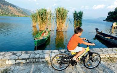 Ποδηλατάδα στον παραλιακό δρόμο που κυκλώνει το Νησάκι. Ιδανικός και για περπάτημα, με σηματοδοτημένα μικρά μονοπάτια προς τις μονές στη λιλιπούτεια ενδοχώρα του. (Φωτογραφία: Βαγγέλης Ζαβός)