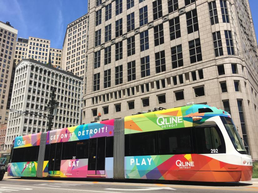 A multi-colored streetcar goes up Woodward avenue, which divides the city from east to west.