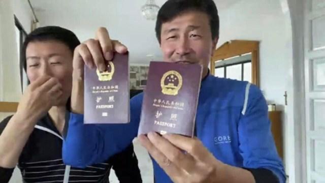 郝海东与妻子叶钊颖在西班牙举起中国护照。(苹果日报图片)