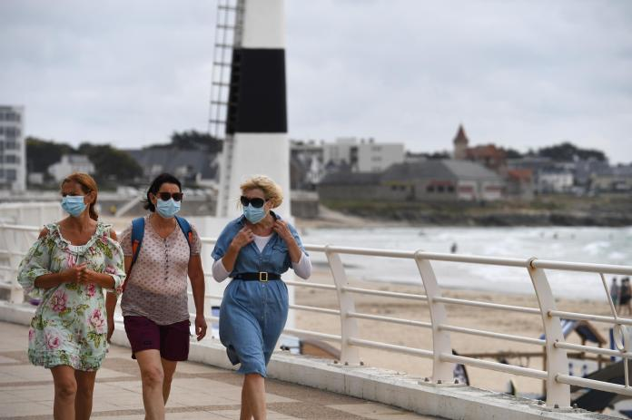 Women wearing masks walk along the seafront on July 27, 2020 in Quiberon, western France
