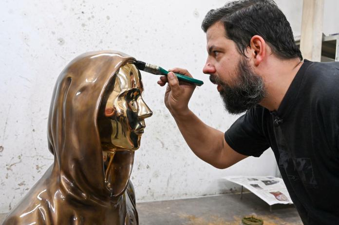 Sculptor Tamas Gilly applies a wax coating to the statue of Satoshi Nakamoto, bitcoin's mysterious inventor