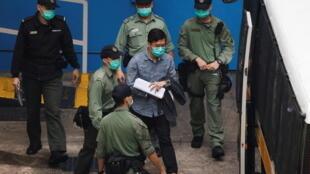图为香港前立法会议员区诺轩2021年3月4日被警方带往法院,与其它40余名民主派人士同天出庭。3月23日他再因扬声器袭警罪名被判监9周。