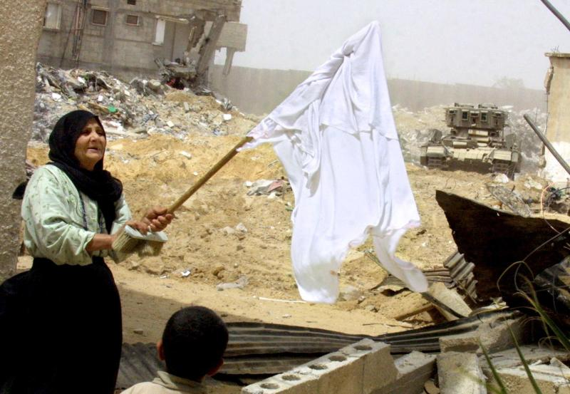 A Palestinian woman raises a white flag as an Israeli armored vehicle heads toward her home in the southern Gaza Strip on May 14, 2004.