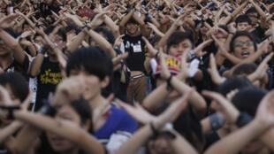 资料图片:2012年香港反国教运动。2012年9月11日,香港中文大学学生以手势表示拒绝政府推行国民教育