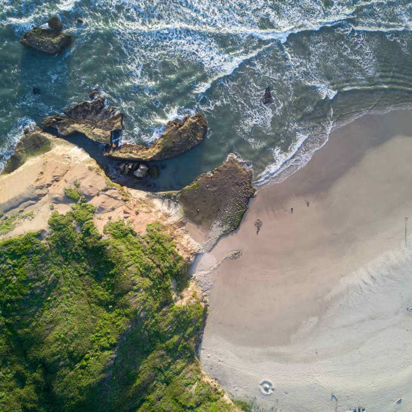 An aerial view of waves crashing against a shore.