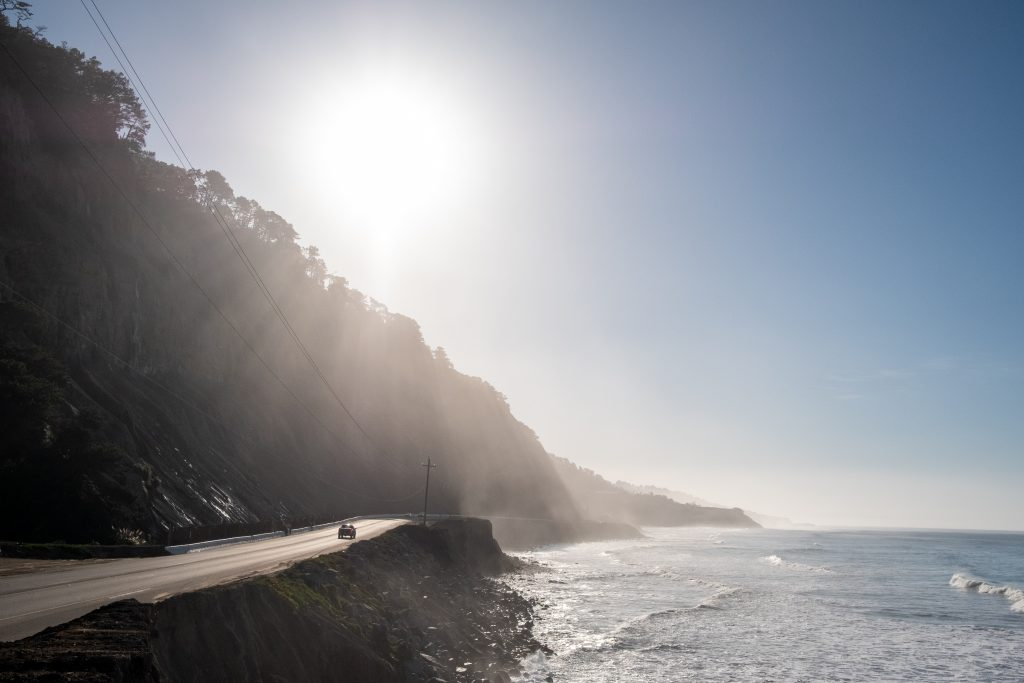 The Sun Shining Over A Ridge Leading Down Into The Shore. In The Distance, A Car Drives Down A Road.