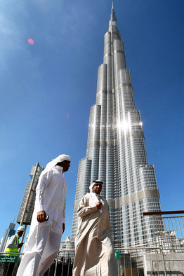 Two men walk past the Burj Dubai on Sunday, the eve of the world's tallest skyscraper's official opening.