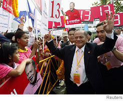 [Thai politician Banharn Silpa-archa makes a sign for 13, the number his party will be using in the general election.]