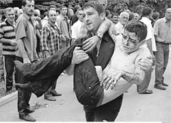 [A wounded boy is carried in Beslan in 2004, when Russian commandos stormed a school where hundreds of hostages were held by Chechen rebels.]