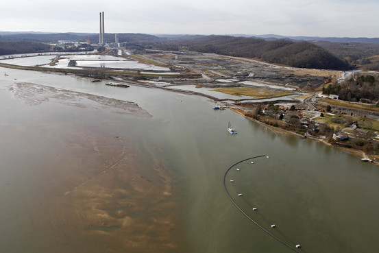 Sediment can be seen in the Emory River as dredging machines pump it and ash into holding ponds to be removed from the water at the plant in Kingston, Tenn., in December 2009.