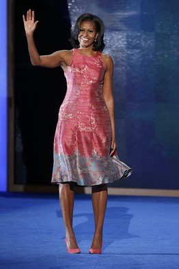 Michelle Obama at second night of 2016 DNC waving in pink and grey dress.