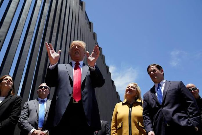 President Donald Trump tours a section of the border wall on Tuesday in San Luis, Arizona, accompanied by Arizona Gov. Doug Ducey (R), second from right, and Rep. Debbie Lesko (R-Ariz), third from right. (Photo: ASSOCIATED PRESS)