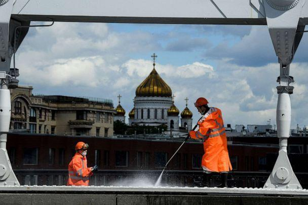 PHOTO: Municipal employees in protective masks clear the Crimean bridge across the Moscow River, in the background is the Cathedral of Christ the Savior in the center of Moscow, Russia, May 20, 2020, during the coronavirus pandemic. (Kirill Kudryavtsev / AFP via Getty Images)