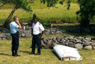 A policeman and a gendarme stand next to a piece of debris from an unidentified aircraft found in the coastal area of Saint-Andre de la Reunion on July 29, 2015 (AFP Photo/Yannick Pitou)