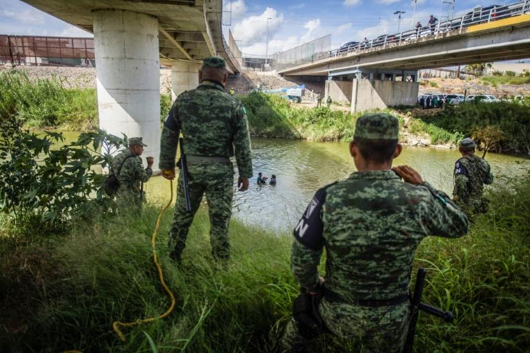Mexican National Guard watch as Central American migrants try to cross the Rio Grande river from Matamoros, Mexico into the United States in July (AFP Photo/CARLOS OGAZ)