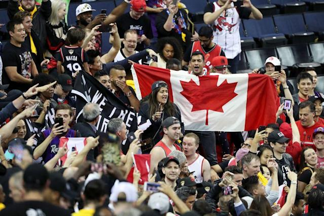 Hundreds, if not thousands, of Raptors fans, surrounded the Oracle Arena court after Game 4. (Getty Images)