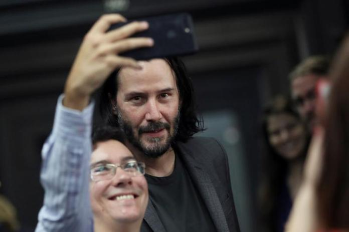 Actor and director Keanu Reeves takes a photo with a fan during a visit to Palacio dos Bandeirantes, seat of the Sao Paulo State Government, in Sao Paulo, Brazil, April 3, 2019. REUTERS/Amanda Perobelli