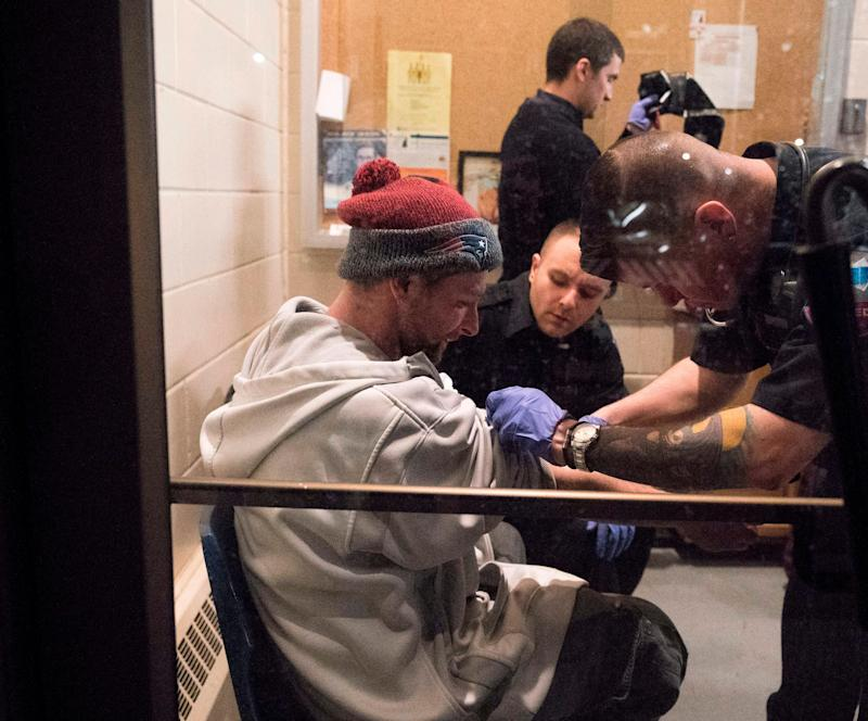 """Thirty one year-old Cody is checked out by paramedics as he enters the Safe Station program at the Central Fire Station March 28, 2018 in Manchester, New Hampshire. Safe Station transformed Manchester's 10 fire stations into intake centers where people struggling with addiction and want to enter treatment and begin their path to recovery can get help without fear of being arrested.Tucked away in the corner of a US fire station are two plastic chairs, a tiny poster saying """"anyone, anytime, can recover,"""" and a poem in memory of a 20-year-old woman who fatally overdosed in 2016. The space is little more than a cubby hole, but has become a safe harbor for drug addicts in New Hampshire and symbol of hope in the US fight against the opioid crisis, a group of drugs, which like morphine, dulls pain and induces euphoria. / AFP PHOTO / Don EMMERT (Photo credit should read DON EMMERT/AFP/Getty Images)"""