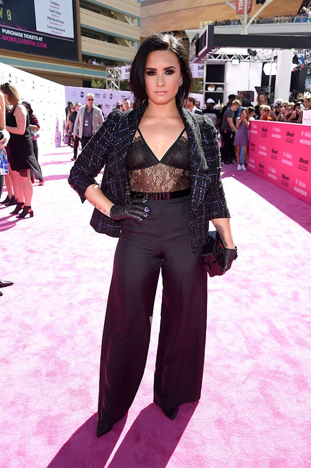 <p>This lacy look is not your typical pantsuit. Lovato, who is set to perform tonight, took her suit to the next level with her signature smoky eye and edgy leather fingerless gloves. <i><b><br /></b></i></p><p><i>(Photo: Frazer Harrison/Getty Images)</i></p>