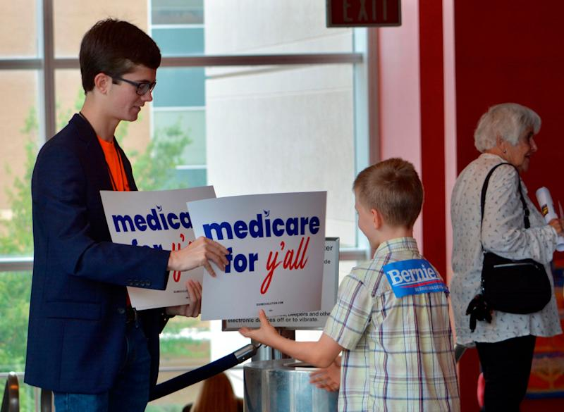 "A volunteer hands out a poster as Vermont independent Sen. Bernie Sanders was set to address a ""Medicare for All"" rally in downtown Columbia, S.C. on Saturday, Oct. 20, 2018. Sanders hasn't announced intentions for another bid in 2020. But in the run-up to the Nov. 6 election, he's visiting more than half a dozen states to stump with congressional candidates. (AP Photo/Meg Kinnard)."